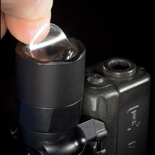 Finger lifting a CLENS Lens Protector off of a weapon light